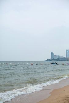 海岸と都市。砂浜を流れる海の泡と波。波の上の水上ボート。
