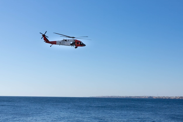 A coast guard helicopter with soldiers flies over the coast of the red sea.