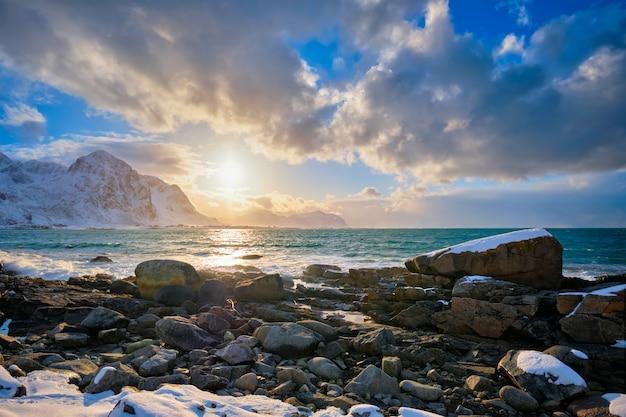 Берег норвежского моря на скалистом берегу во фьорде на закате