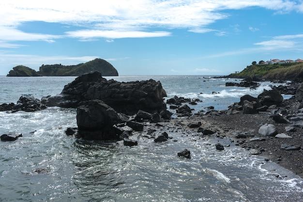 Coast rocks in azores. waves splashing on basalt rocks