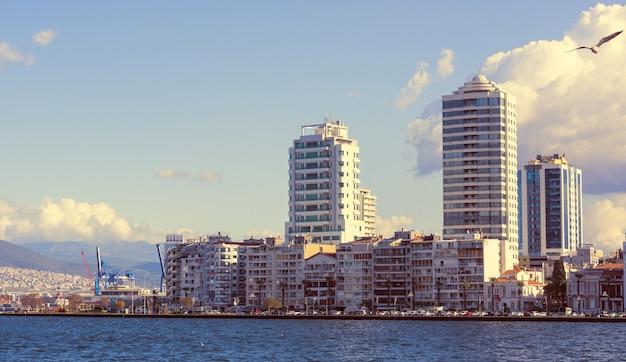흐린 하늘 아래 현대적인 건물이 있는 해안 도시. 터키 이즈미르 시