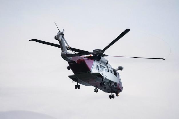 스코틀랜드에서 바다 위로 비행하는 해안 경비대 헬리콥터