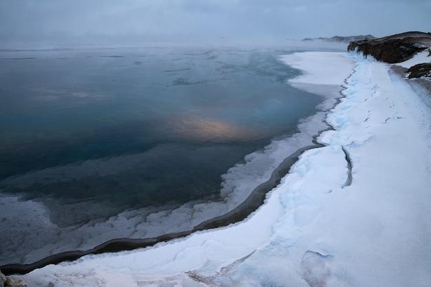 바람이 부는 아침에 겨울에 얼어 호수의 해안선