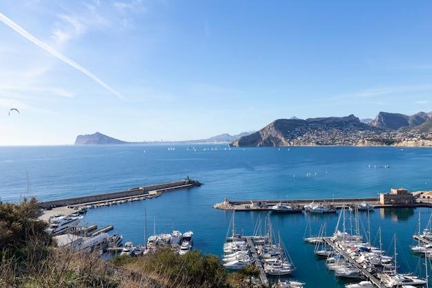 海とヨット、湖の高層ビルと山のあるカルペスペインの地中海リゾートの海岸線...