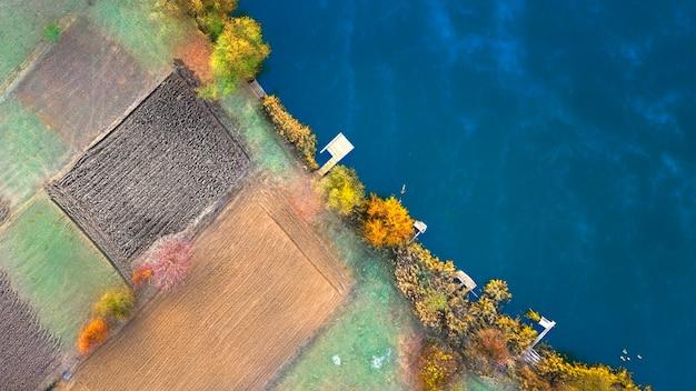 Coastline with empty garden plots and yellow autumn trees
