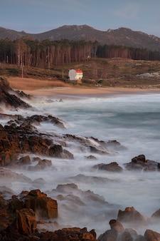 Береговая линия с камнями на берегу во время заката