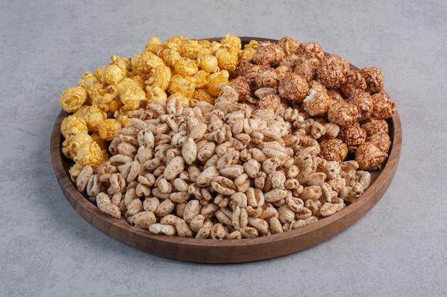 Caramelle e fiocchi di popcorn ricoperti su un vassoio su marmo.