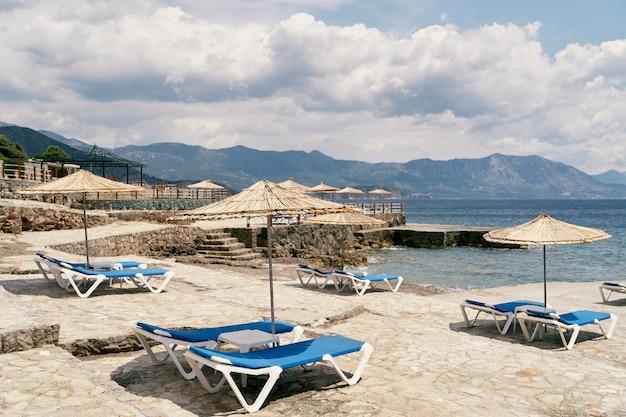 바다 근처에 일광욕용 라운저와 파라솔이 있는 자갈 해변