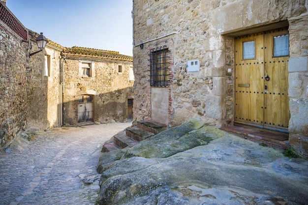 Cobblestone pathway surrounded with old buildings under a sunlight
