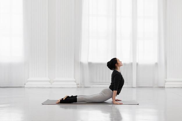 Cobra pose beautiful young asian woman practicing yoga pose on gray mat at yoga studio
