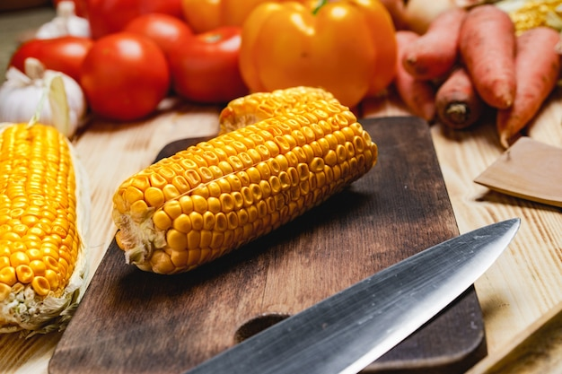 Cobs of corn on wooden cutting board on table
