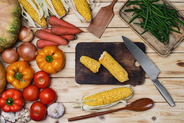 Cobs of corn on wooden cutting board