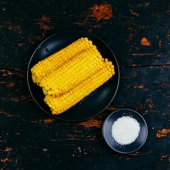Початки вареной кукурузы и соли на черной тарелке на деревянном винтажном черном столе