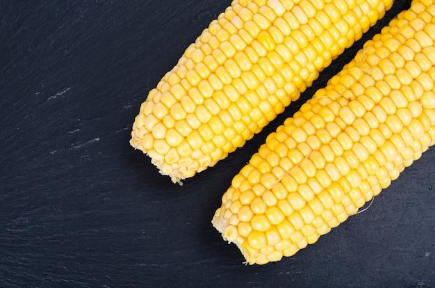 Cobs of ripe yellow sweet corn on black background. studio photo.