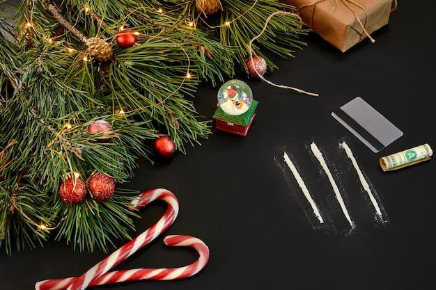 黒の背景の上面図にクリスマスのおもちゃとトウヒの枝でパスに分割されたコカイン