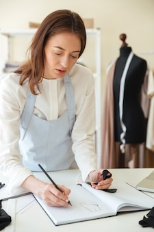 新しいアートワークを描く青いエプロンで集中女性仕立て屋