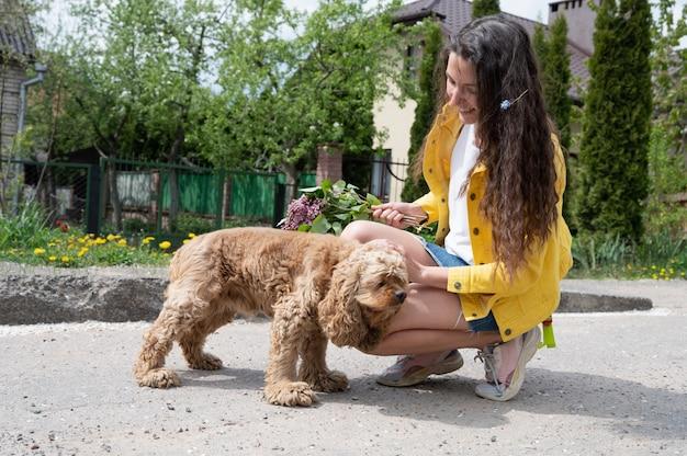 通りを女の子と歩いているコッカースパニエル。