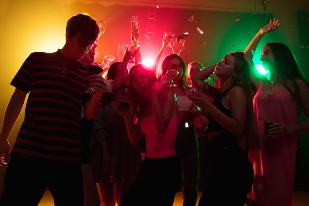 칵테일. 실루엣의 사람들이 손을 들고 네온 불빛 배경의 댄스플로어에서 춤을 춥니다. 나이트 라이프, 클럽, 음악, 댄스, 모션, 젊음. 밝은 색상과 움직이는 소녀와 소년.