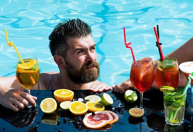 プールでカクテルとひげを生やした男