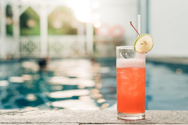 スイミングプールの端にあるカクテル。スイミングプールの背景にオレンジ色のスライスを持つ赤いカクテル。ヴィンテージエフェクトスタイルの写真。