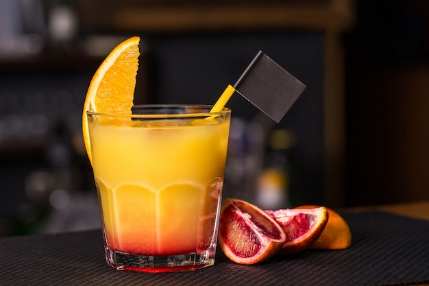 Cocktail on the bar table with orange