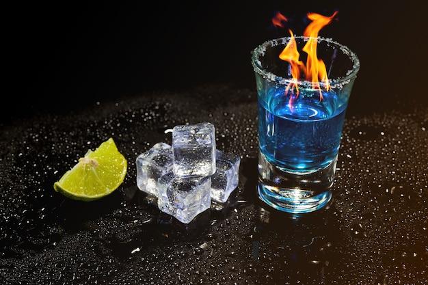 Коктейль синий горит в рюмке с солью и известью, кубики льда на черной поверхности.