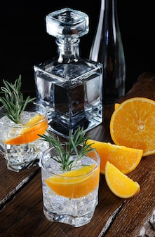 슬라이스 육즙 오렌지와 나무 보드에 로즈마리의 장식과 토닉과 오렌지 풍미와 칵테일 클래식 드라이 진