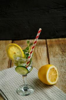 Коктейль огуречная вода с лимоном и мятой в стакане на салфетке на черной поверхности возле лимона и огурца