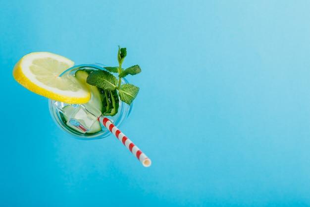 Коктейль из огуречной воды с лимоном и мятой в стакане на салфетке на синей поверхности, вид сверху
