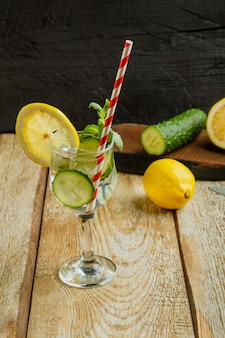 Коктейль из огуречной воды с лимоном и мятой в стакане на деревянном столе на черной поверхности рядом с лимоном и огурцом