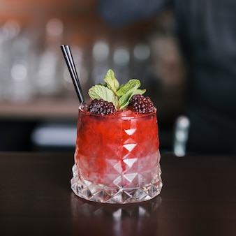 Cocktail decorated with blackberries and mint