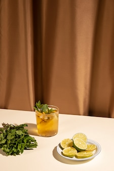 Cocktail drink glass with mint leaves and slices of lime on white table against brown curtain