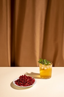 茶色のカーテンの前にテーブルの上の皿にザクロの種子とカクテルドリンクグラス
