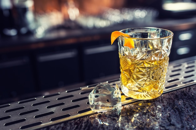 Cocktail drink old fashioned at barcounter in night club or restaurant.