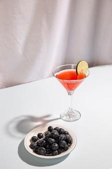 白い背景のプレートに青い果実とカクテルを飲む