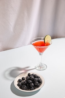 Cocktail drink with blue berries on plate against white background