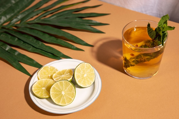 Cocktail drink with lemon slices and palm leaf over brown desk