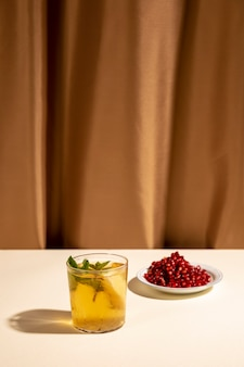 Cocktail drink with pomegranate seeds on white table