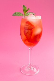 Cocktail drink with strawberry and ice in a glass on the pink  background. location vertical. closeup.