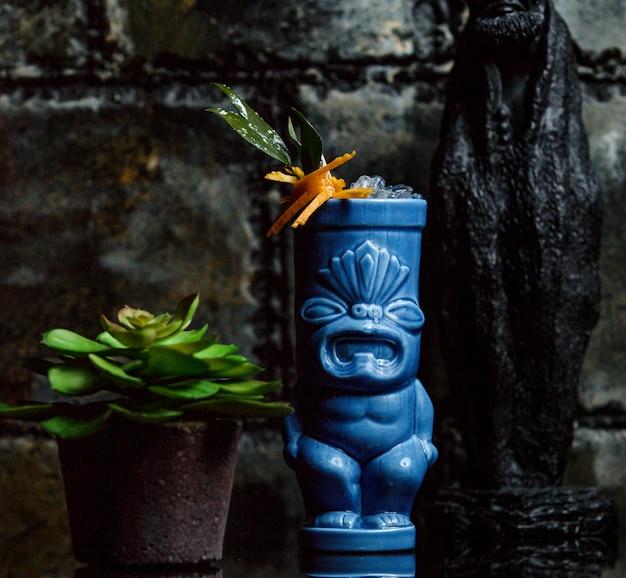 Cocktail garnished with orange in blue cocktail mug