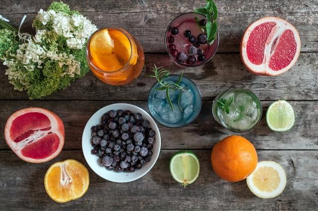 Коктейль gin tonic, mojito и aperol spritz с мятой, льдом, лаймом, ягодами, грейпфрутом и апельсином на деревянном фоне.