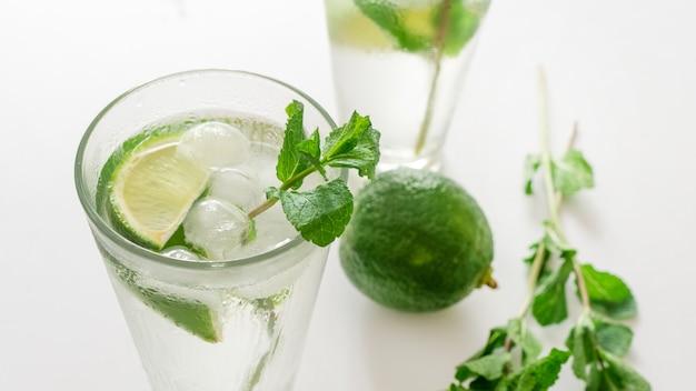 Коктейль джин-тоник или мохито в стакане с мятой, льдом, лаймом на белом фоне.