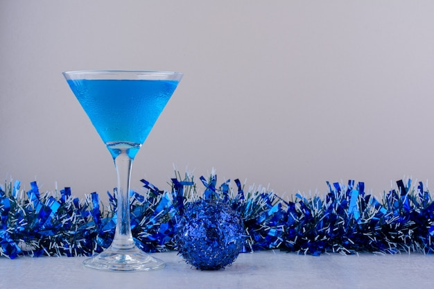 Cocktail glass next to blue christmas decorations on white background.