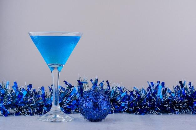 Bicchiere da cocktail accanto a decorazioni natalizie blu su sfondo bianco.