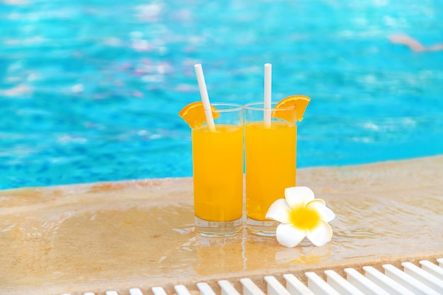 Cocktail in a glass by the pool and fruits