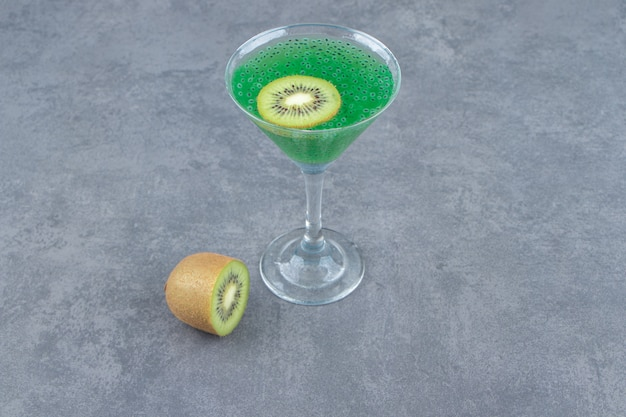 A cocktail glass cup of kiwi juice with a slice of fruit. high quality photo