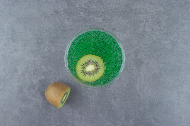 A cocktail glass cup of kiwi juice with a slice of fruit.
