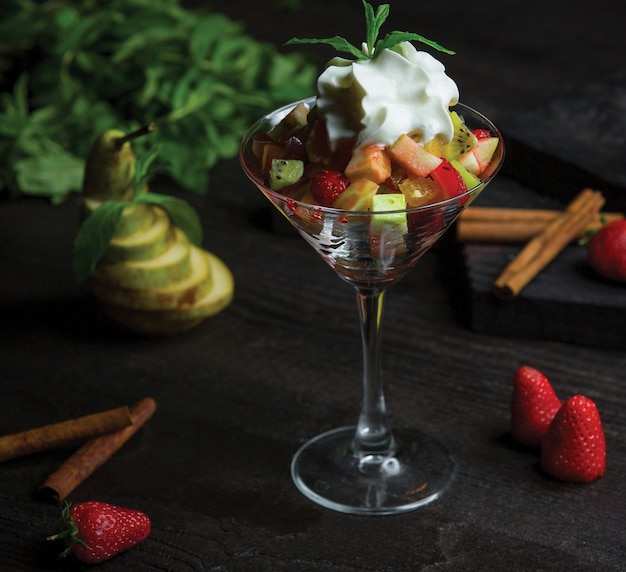 A cocktail glass full of fruit salad and whipped cream