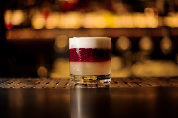 Бокал для коктейля из разноцветного хлопьевидного сладкого и вкусного коктейля
