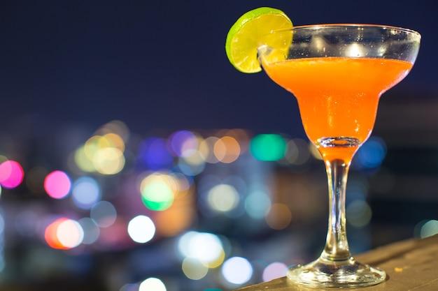 金の石のテーブルの上のオレンジ色のマルガリータレモン装飾のカクテルグラスは、街並みのボケ味の背景をぼやけさせました。